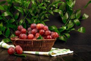 rote Trauben in einem Weidenkorb auf Holzoberfläche