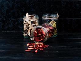 Gläser mit getrockneten Früchten auf dunklem Hintergrund