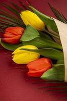 roter und gelber Blumenstrauß auf rotem Grund