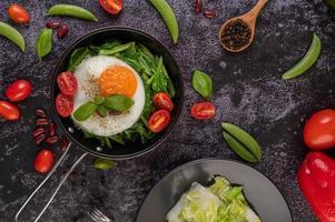 Grünkohl in einer Pfanne mit Ei und Tomaten umrühren