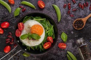 Grünkohl in einer Pfanne mit Ei umrühren