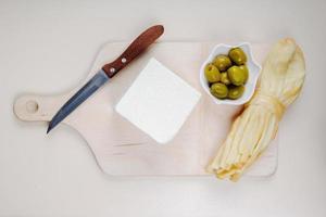 Draufsicht von Käse und Oliven auf einem Schneidebrett