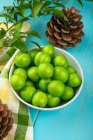 saure grüne Pflaumen und Tannenzapfen foto