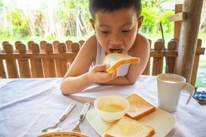 Junge, der Brot isst foto