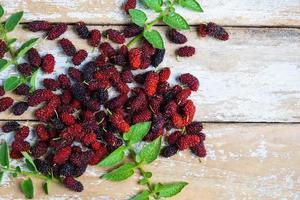 Maulbeeren und Blätter auf einem Tisch