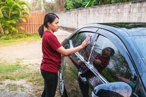 Frau, die draußen ein Auto wäscht foto