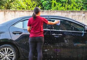 Frau, die tagsüber ein Auto wäscht foto
