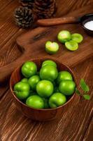 saure grüne Pflaumen in einer Holzschale und einem Schneidebrett auf einem Holztisch foto