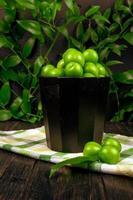 Eimer mit sauren grünen Pflaumen foto