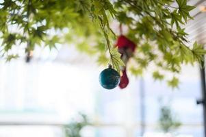 Nahaufnahme einer blauen Kugel, die vom Weihnachtsbaum hängt