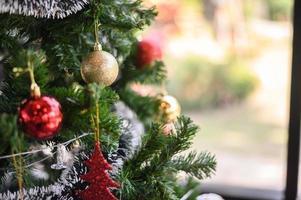 Nahaufnahme einer goldenen Kugel, die vom Weihnachtsbaum hängt
