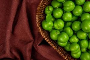 grüne Pflaumen in einem Weidenkorb auf dunkelrotem Stoff foto