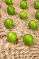 Gruppe von sauren grünen Pflaumen auf Sackleinen foto