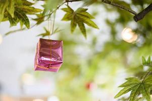 Nahaufnahme einer rosa Geschenkbox, die vom Weihnachtsbaum hängt