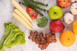 Draufsicht auf Äpfel, Orangen, Brokkoli, Babymais, Trauben und Tomaten foto