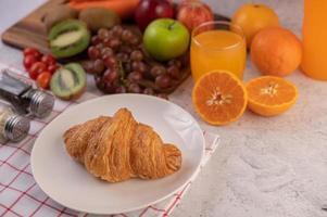 Croissant mit Frühstücksfruchtseiten foto
