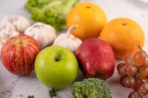 Nahaufnahme von Äpfeln, Orangen, Brokkoli, Babymais, Trauben und Tomaten foto