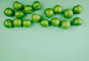 grüne saure Pflaumen auf einem grünen Hintergrund mit Kopienraum foto