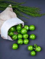 grüne Pflaumen und Fenchel auf einem schwarzen Hintergrund foto