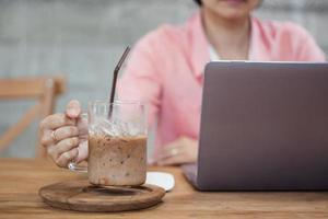 Frau, die einen Kaffee hält, während sie an einem Computer arbeitet foto