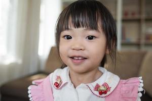 Porträt eines kleinen asiatischen Mädchens, das in ihrem Haus spielt foto