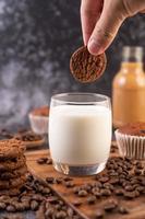 Hand, die einen Keks in Milch taucht