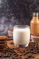 Milch in einem Glas mit Kaffeebohnen und Muffins