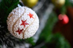 Nahaufnahme einer weißen Kugel, die vom Weihnachtsbaum hängt