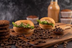 Burger mit Kaffeebohnen auf einer braunen Holzplatte foto