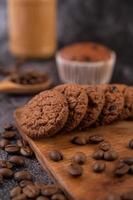 Kekse mit Kaffeebohnen auf einem Holzbrett