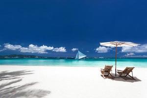 Sonnenschirme und Holzbetten am tropischen Strand foto