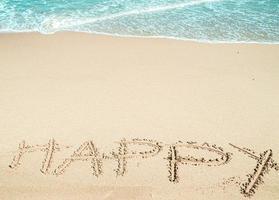 glücklich in Sand geschrieben