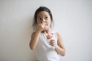 Porträt eines kleinen Mädchens, das Eis isst foto