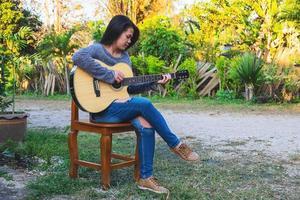 Frau sitzt auf einem Stuhl und spielt Gitarre