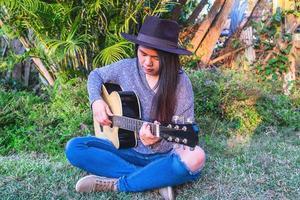 Frau in einem Garten, der Gitarre spielt foto