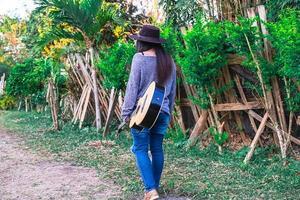 Frau, die in einem Garten mit einer Gitarre geht
