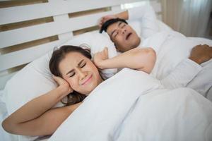 schlafende Frau blockiert die Ohren mit Mann, der im Bett schnarcht