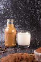 Kaffee in einer Flasche mit Milch in einem Glas