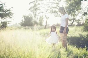 Mutter und kleine Tochter spielen auf einem Feld im Sonnenlicht foto