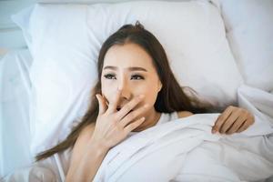 Frau wacht in ihrem Bett auf, faul am Morgen