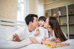 glückliches Kind mit Eltern, die zu Hause spielen foto