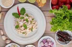 Hühnersalat auf einem weißen Teller mit Minzblättern foto