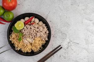 gehacktes Schweinefleisch in einer Pfanne mit Limette, Chilis und Fleischbällchen