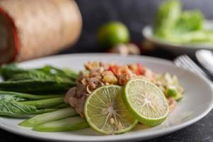 würziger Limettenschweinefleischsalat auf einem grünen Bett