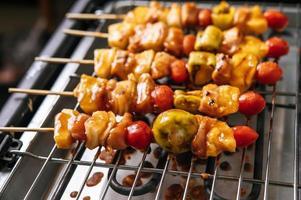 Grill mit einer Vielzahl von Fleisch, Tomaten und Paprika