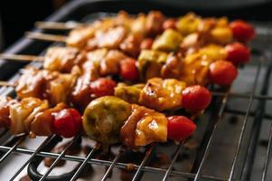 Grill mit einer Vielzahl von Fleisch, Tomaten und Paprika foto