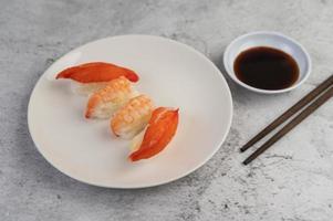 plattiertes Sushi mit Sauce und Essstäbchen foto