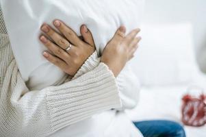 Person, die ein weißes Kissen auf dem Bett umarmt