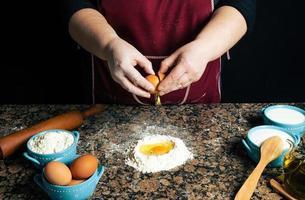 Person, die Eier in Mehl knackt
