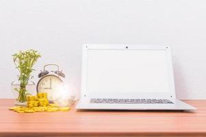 Laptop und Münzen auf dem Schreibtisch